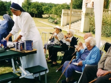 Sisters and residents sip tea at the care home's garden party. Credit: Laxton Hall