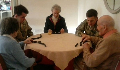 Left-right: Trooper Stephen Dixon and Private Burnikell play dominos with residents Credit: Daniel Burnikell